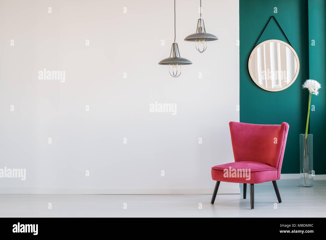 Lamps Above Red Chair And Dandelion Against Green Wall With Round Mirror In  Living Room Interior