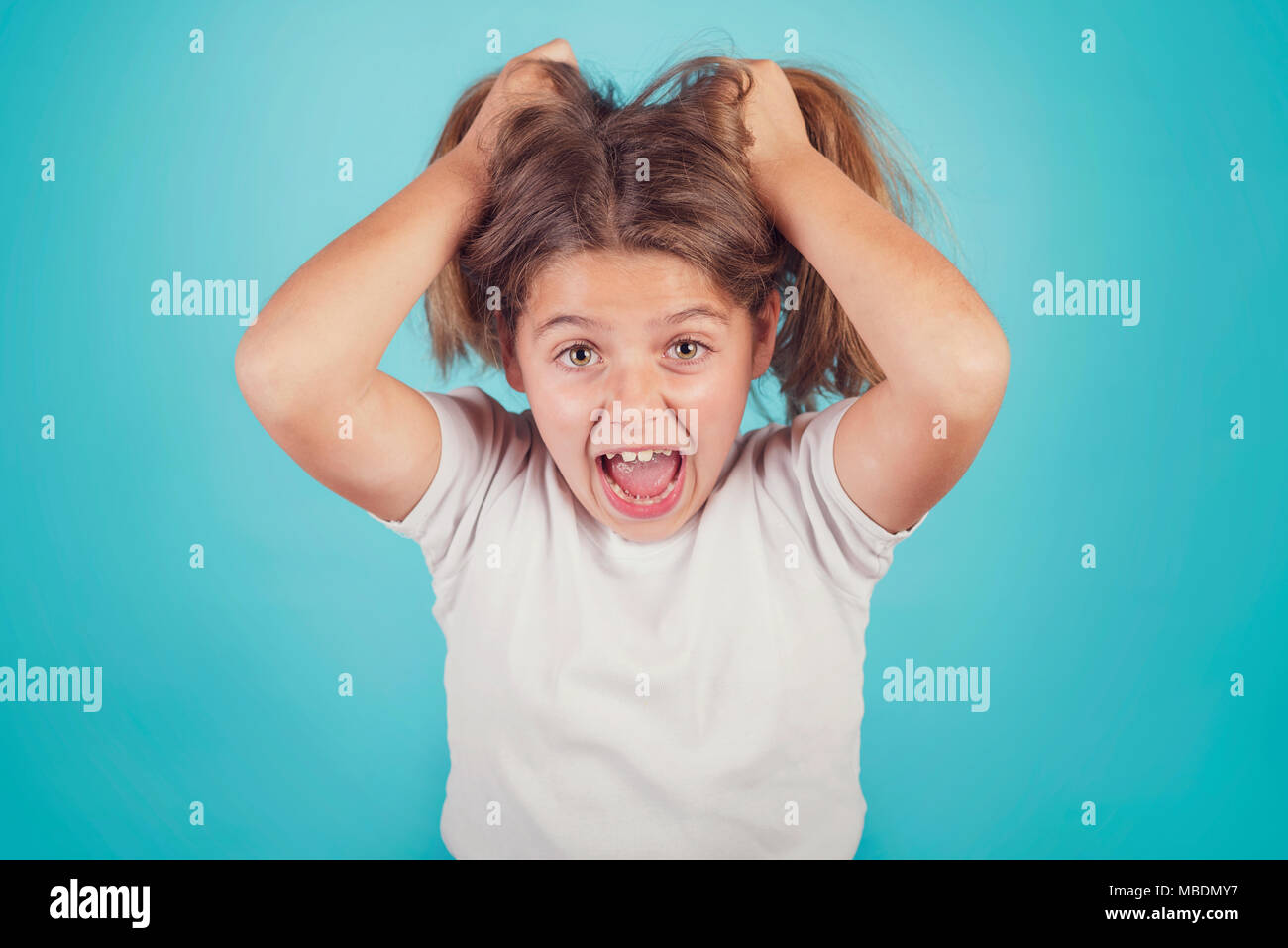 portrait of angry girl on blue background - Stock Image