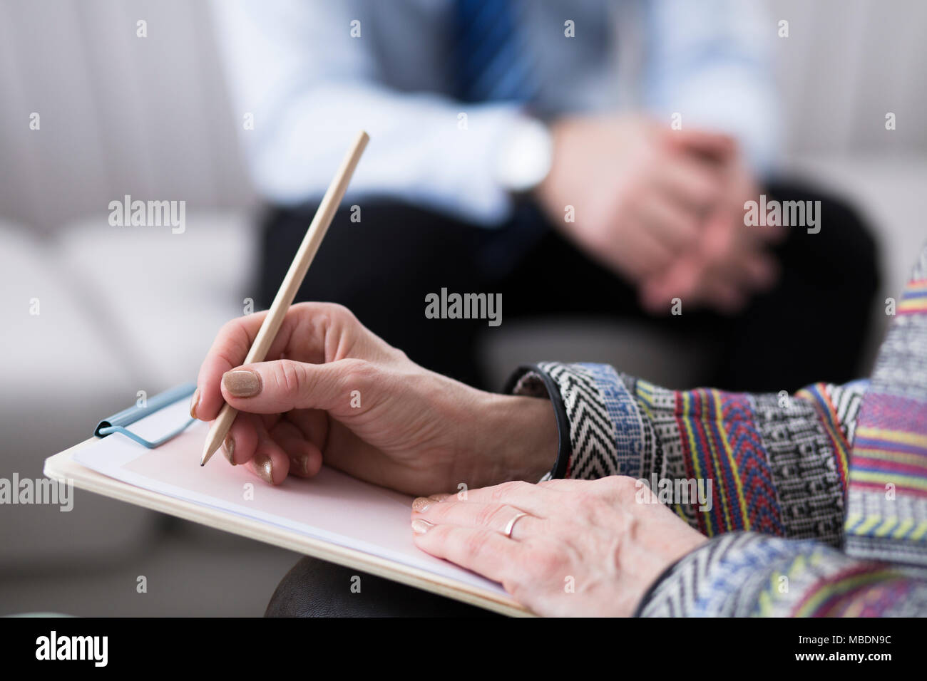 Close-up of psychotherapist writing notes while analyzing her patient Stock Photo