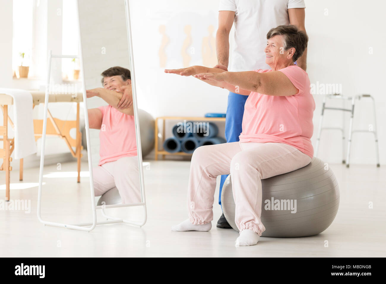 Smiling senior exercising with a physiotherapist on a silver ball at a white gym - Stock Image