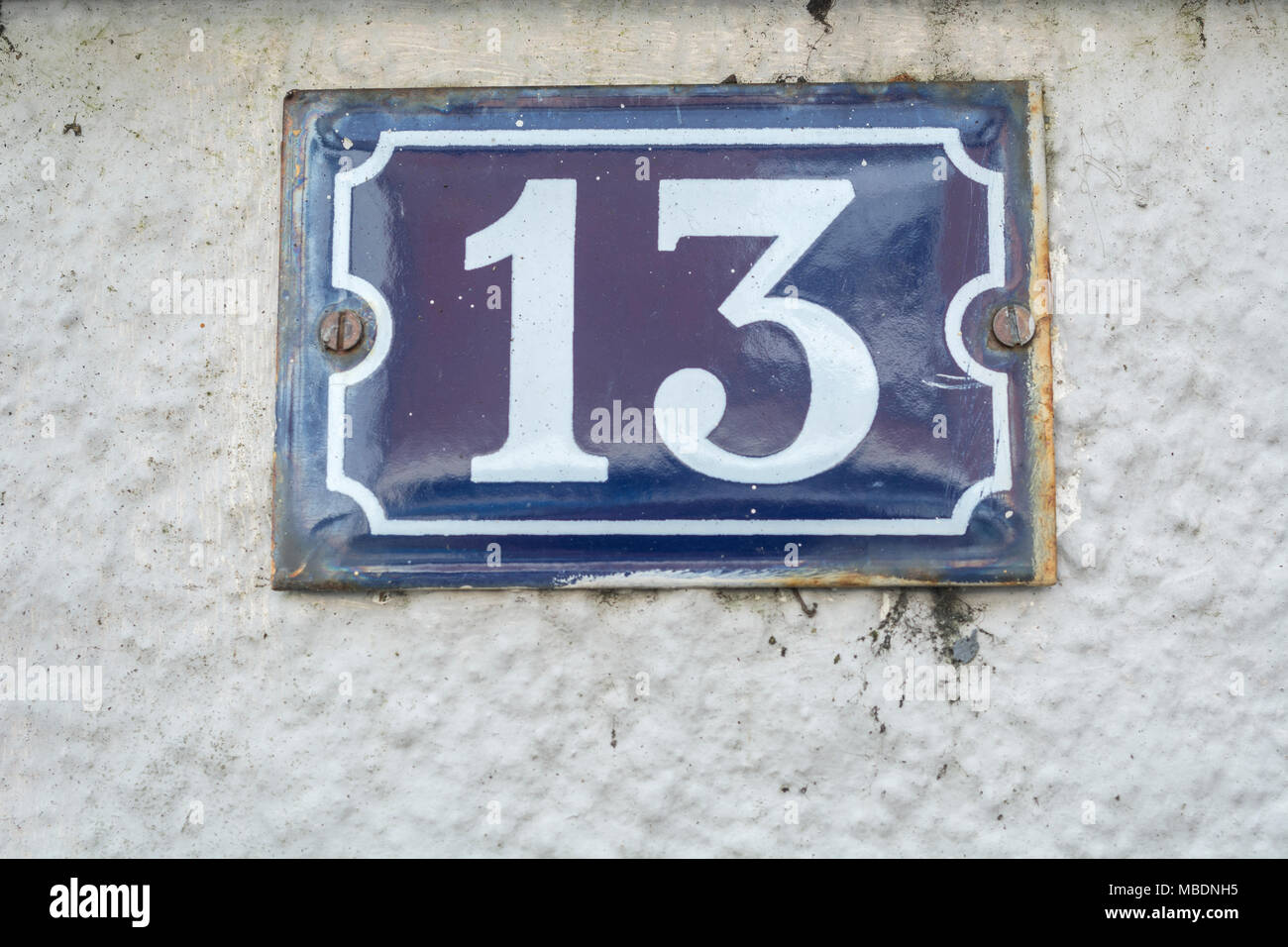 Enamel house number - No. 13 (unlucky for some). Odd number. - Stock Image