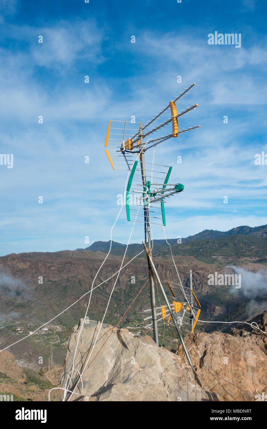 TV aerial on rock above houses in deep mountain valley in Spain - Stock Image