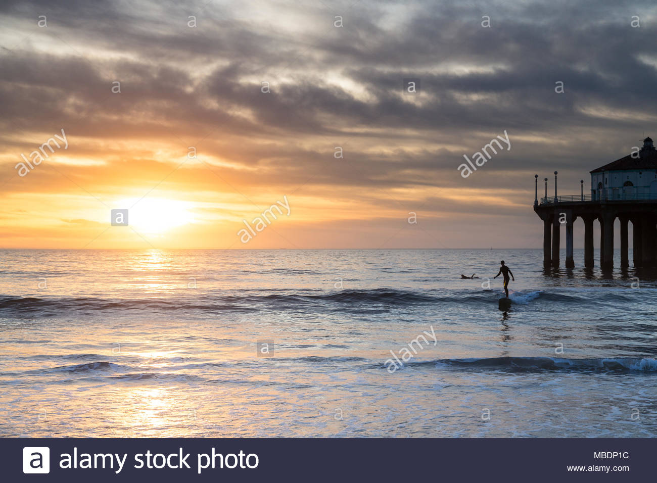 A longboard surfer catches one last wave next to the Manhattan Beach Pier on a cloudy day. - Stock Image