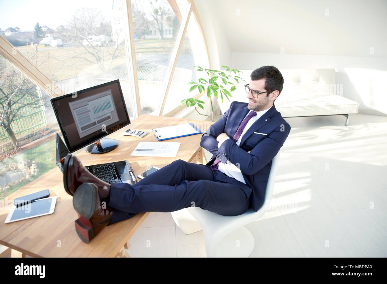Full length shot of successful young businessman wearing suit while sitting at his modern office with his legs on office desk. - Stock Image