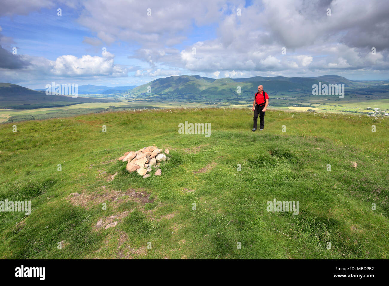 Walker at the summit of Great Mell Fell, Lake District National Park, Cumbria County, England, UK - Stock Image