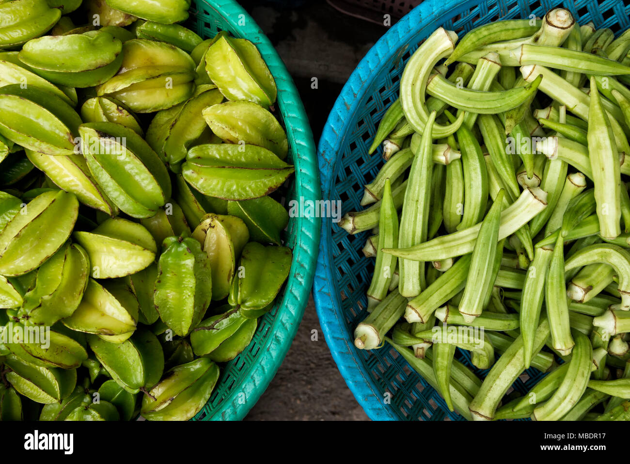 Baskets of star fruits and okra - Stock Image