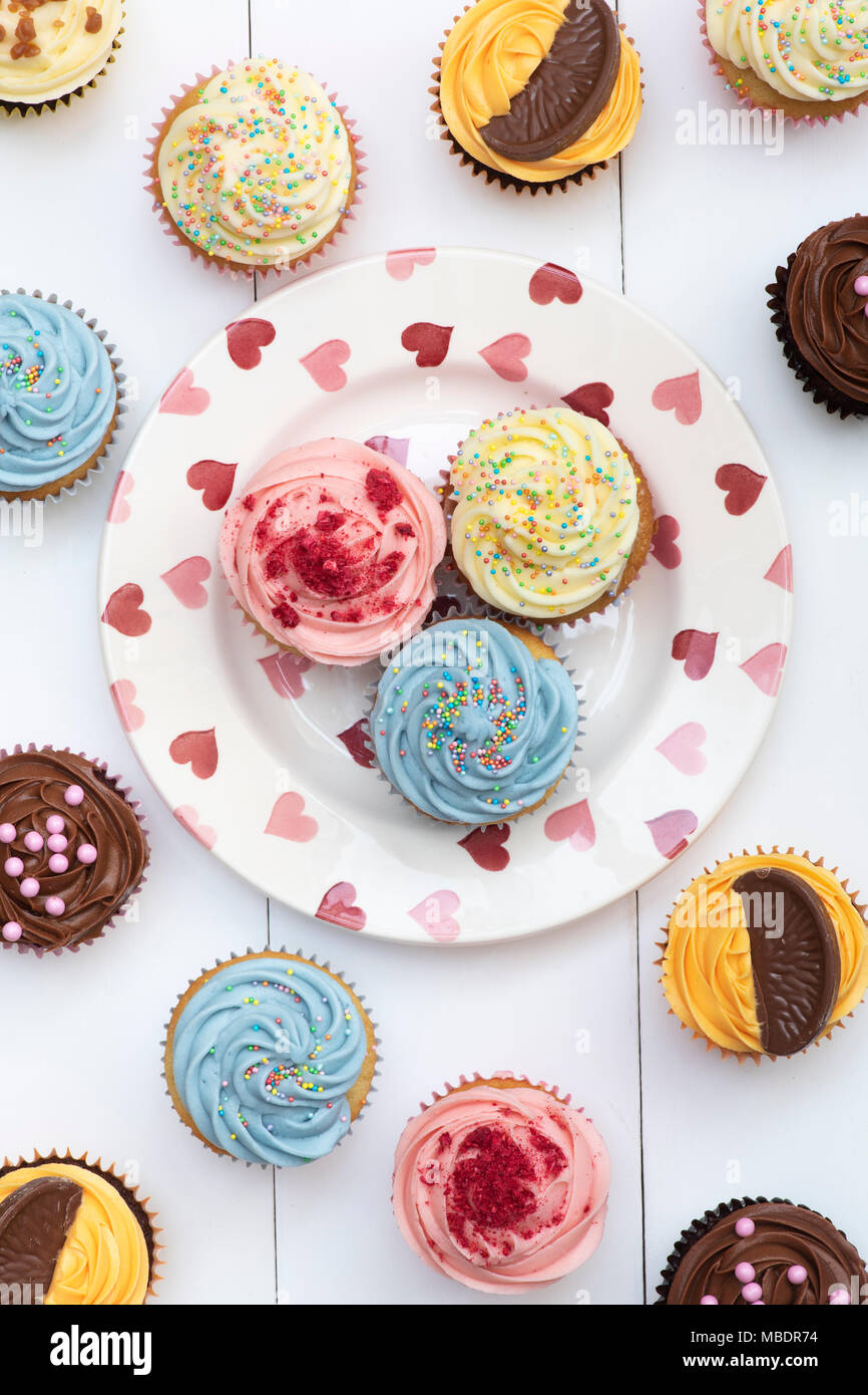 Colourful cupcakes on a heart pattern plate pattern - Stock Image