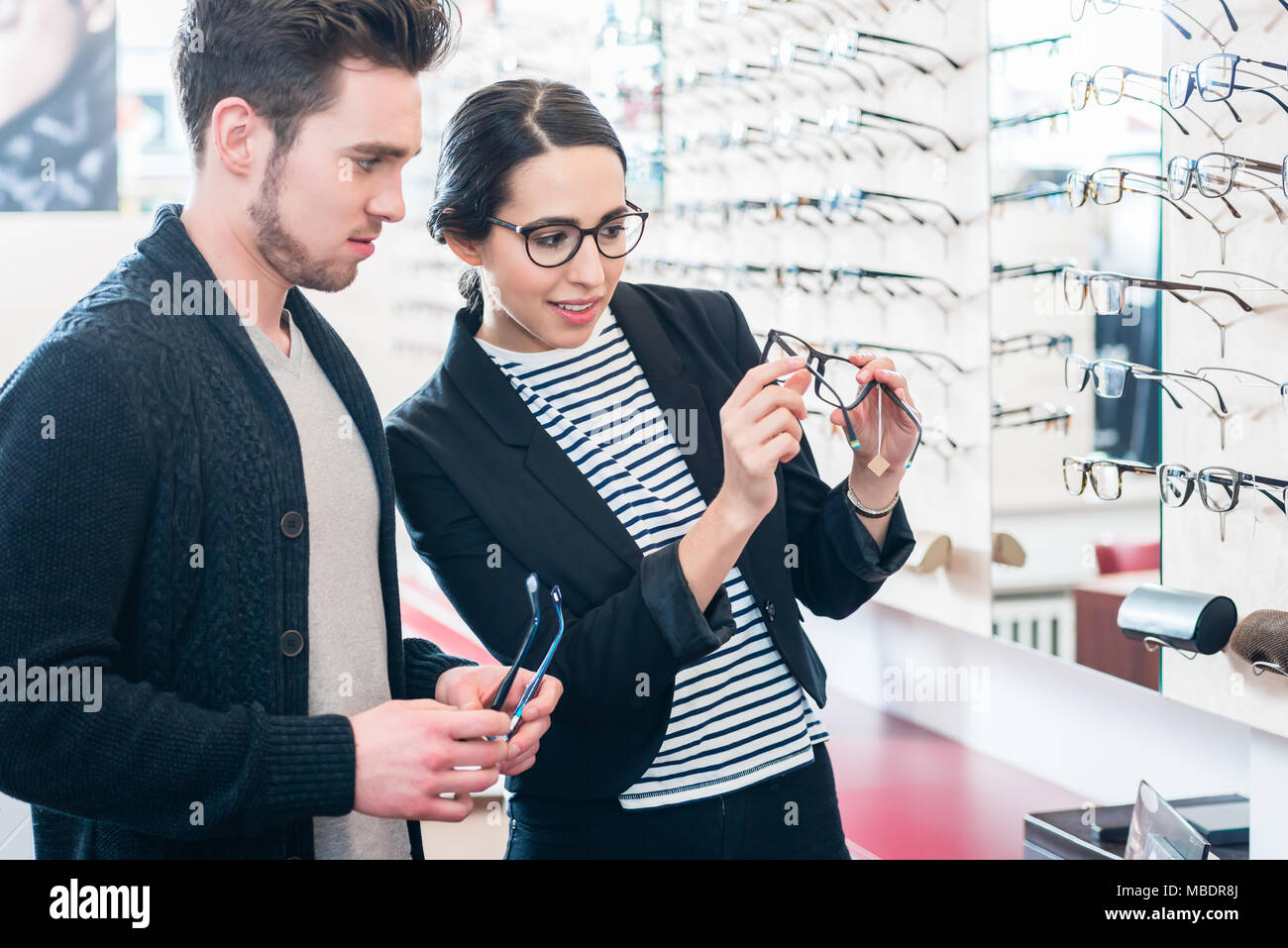 Woman and man buying glasses in optician shop - Stock Image
