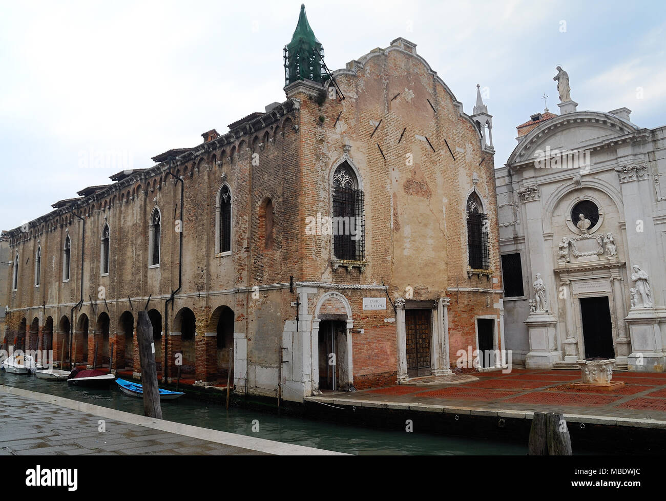 Venice, Italy. The Church of the Abbey of Misericordia (Chiesa dell' Abbazia della Misericordia) is a religious edifice in Venice, Italy, in the sestiere Cannaregio. It was founded in the 10th century. The façade was restored in 1659 by the patrician Gaspare Moro. It is decorated by allegoric statues, including a bust of Moro, all work by Clemente Molli. On the right is a 13th-century bas-relief depicting the Madonna with Child. The church was in dismaying condition in the 19th century, and was restored until 1864. It is adiacent to the Scuola vecchia della Misericordia. - Stock Image