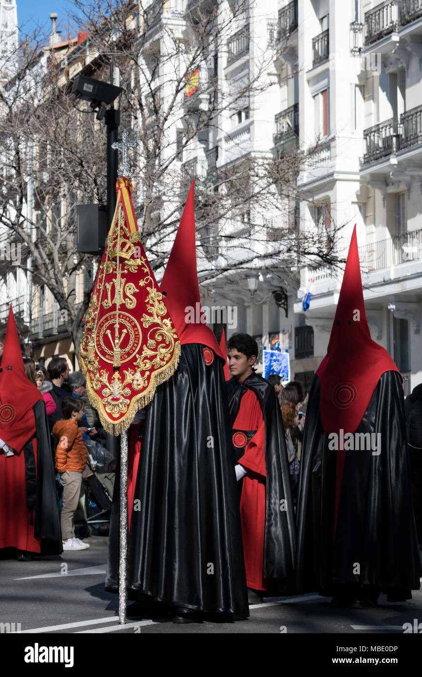 Penitents in hoods and robes carry a banner in an Easter parade on Holy Saturday, Semana Santa (Holy Week) parades, Madrid, Spain, 2018 - Stock Image