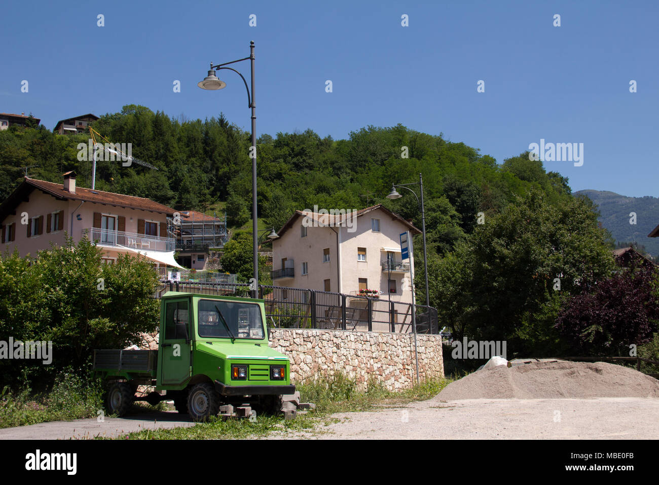 A small green work truck parked in San Lorenzo, Italy Stock Photo