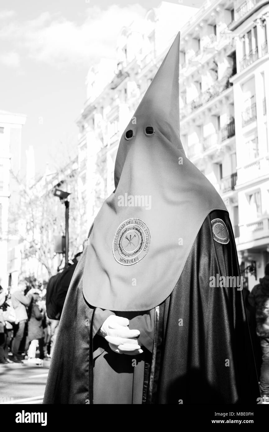 Penitent in traditional hood and robe in an Easter parade on Holy Saturday, Semana Santa (Holy Week) parades, Madrid, Spain, 2018. Black and white - Stock Image