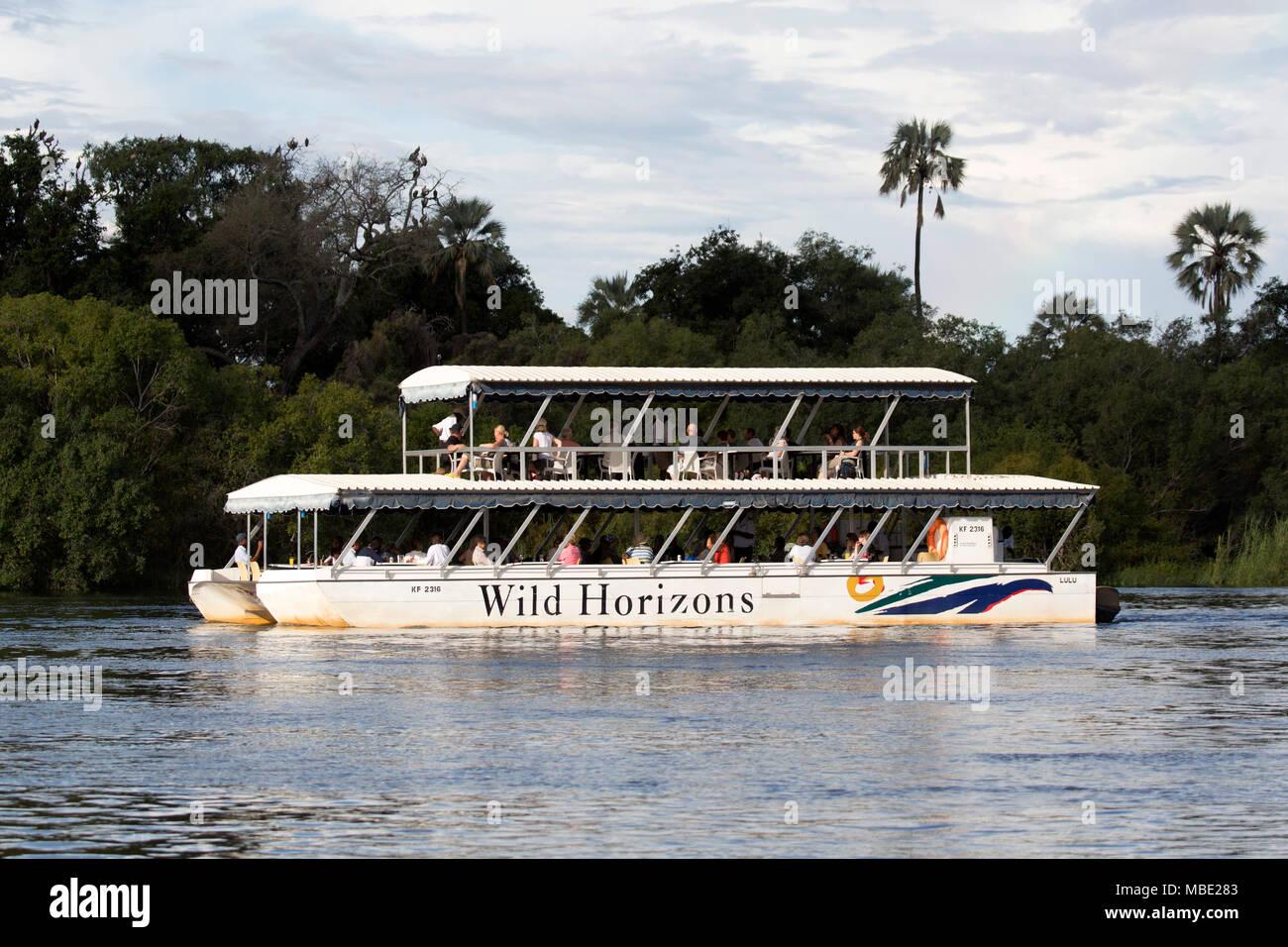 A Wild Horizons boat during a sunset cruise on the Zambezi River near Victoria Falls in Zimbabwe. - Stock Image