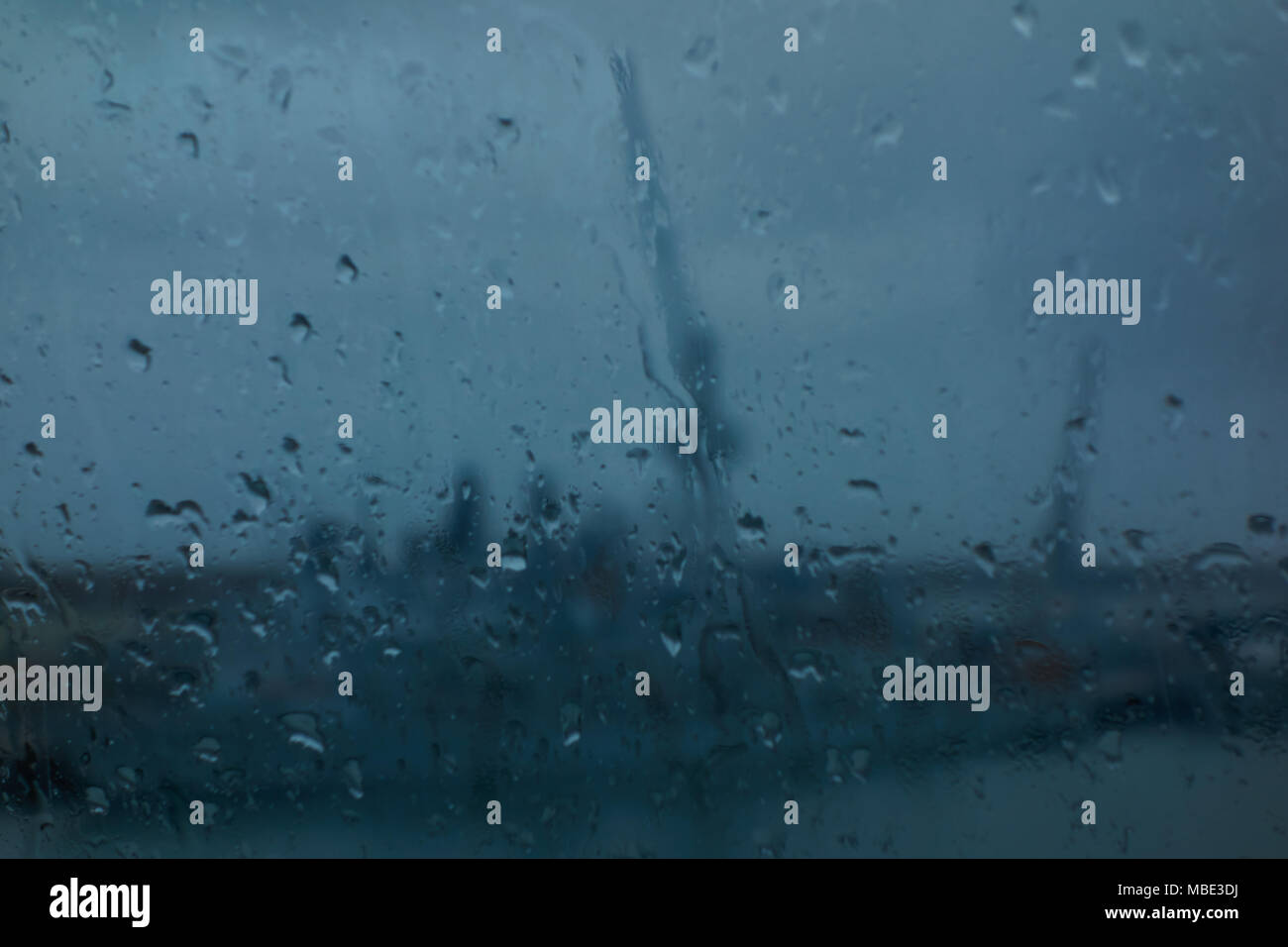 Rain on a window overlooking a harbour - Stock Image