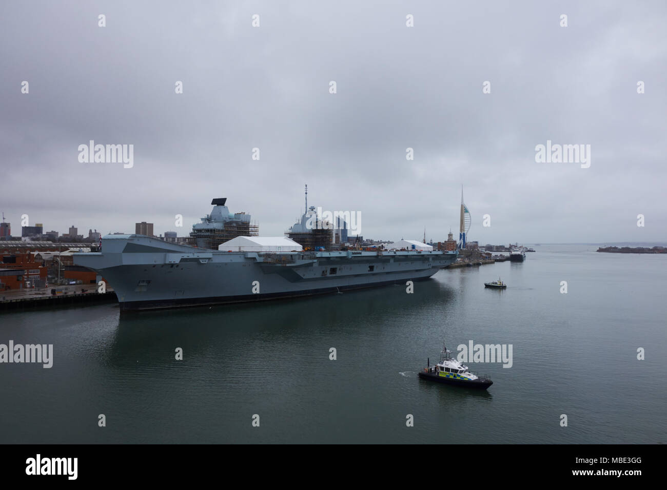 Port view of Royal Navy HMS Queen Elizabeth under maintenance, with police patrol boats on guard in Portsmouth, UK - Stock Image