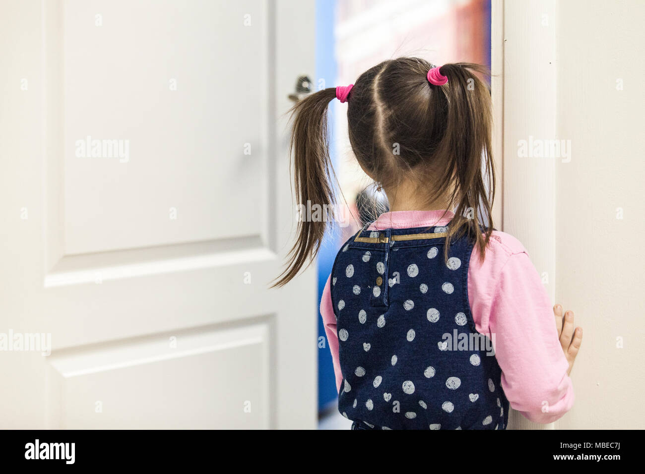 Girl (5-7) looking into classroom through the door rear view - Stock Image