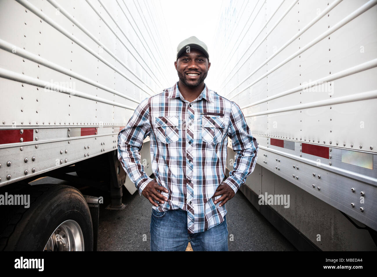A truck driver standing between two large truck trailers in a trailer park, hands on hips, smiling, working clothes - Stock Image