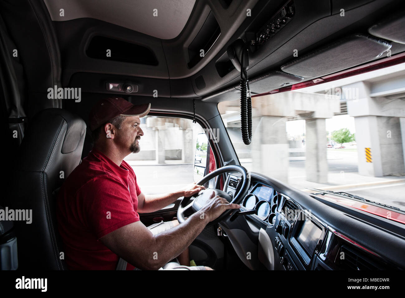 Interior cab view of a Caucasian man driving his commercial truck