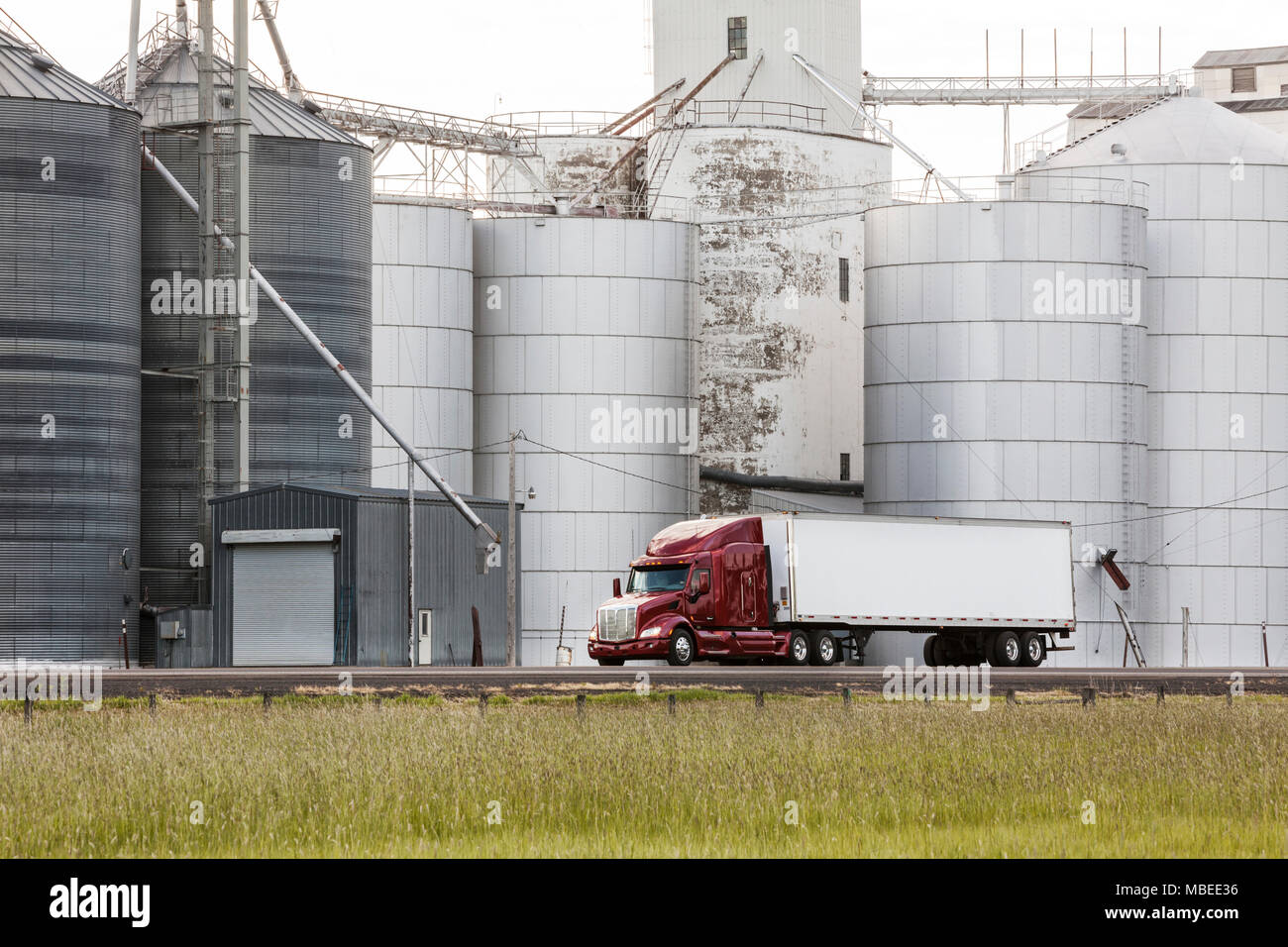 A commercial truck driving past grain elevators in the farm country of eastern Washington, USA. - Stock Image