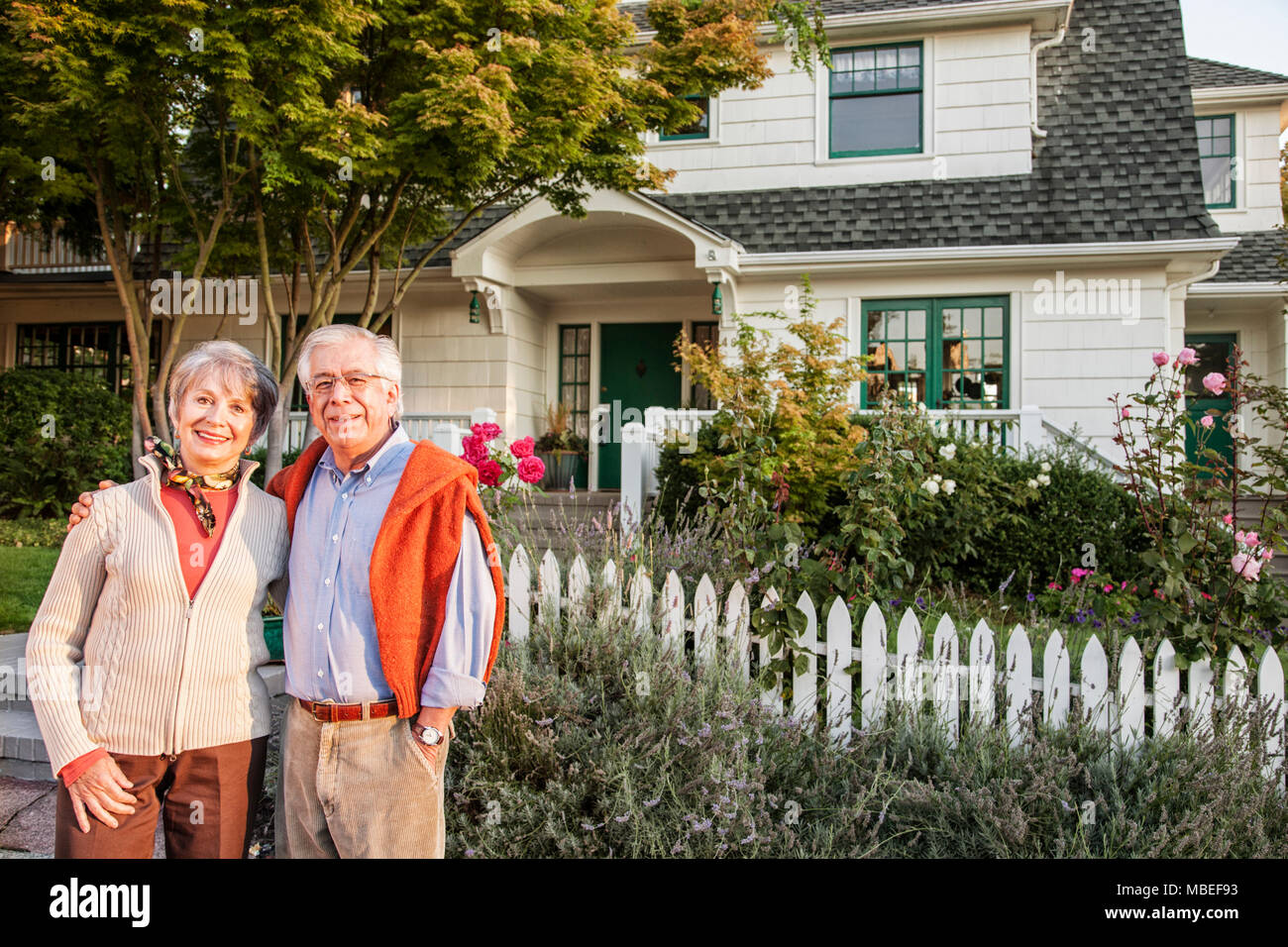 Hispanic senior couple in front of their remodeled older style home. - Stock Image