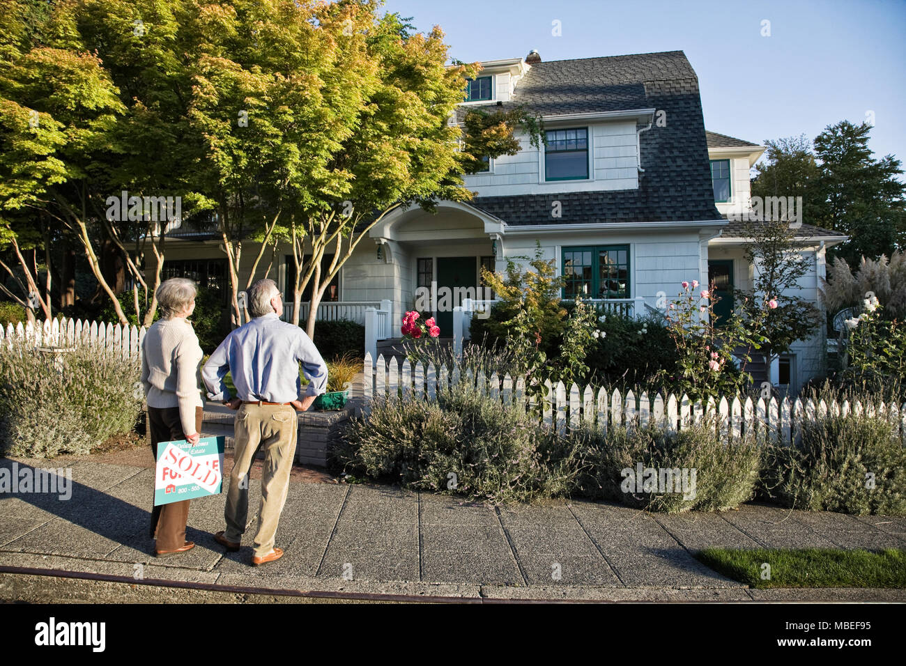 HIspanic seniors in front of their newly puchased remodeled older style home. - Stock Image