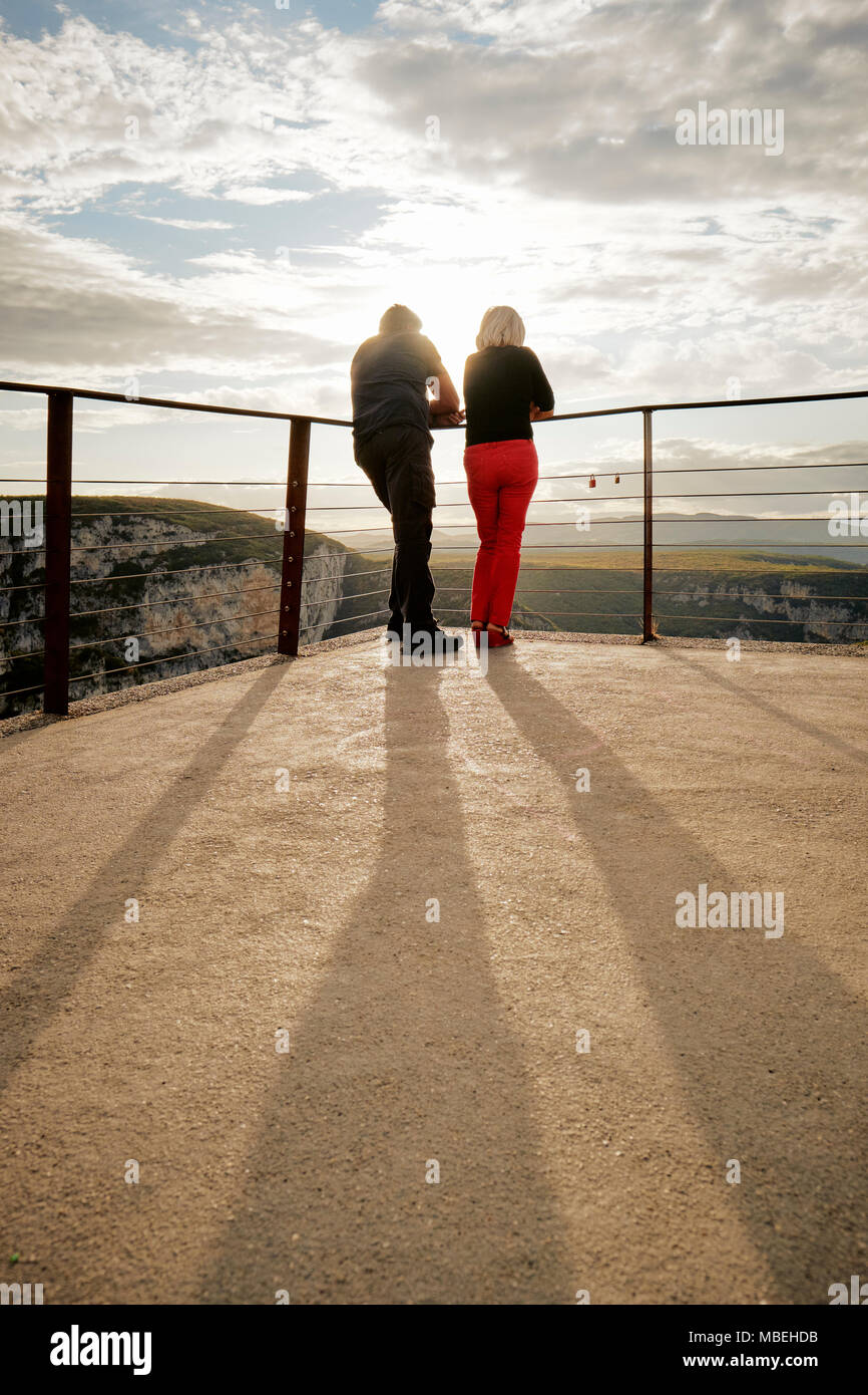 Two people at a viewpoint backlit by the low evening sun - Stock Image