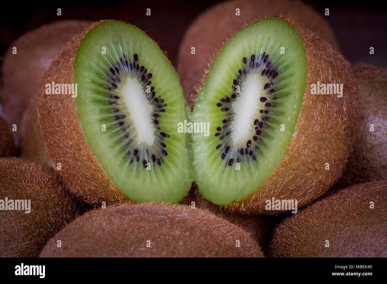 Slit open kiwi fruit - Stock Image