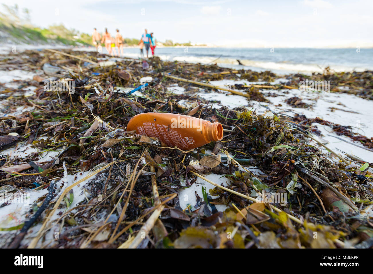 Plastic waste lies washed up on the shore of a white sand beach with people walking in the background - Stock Image