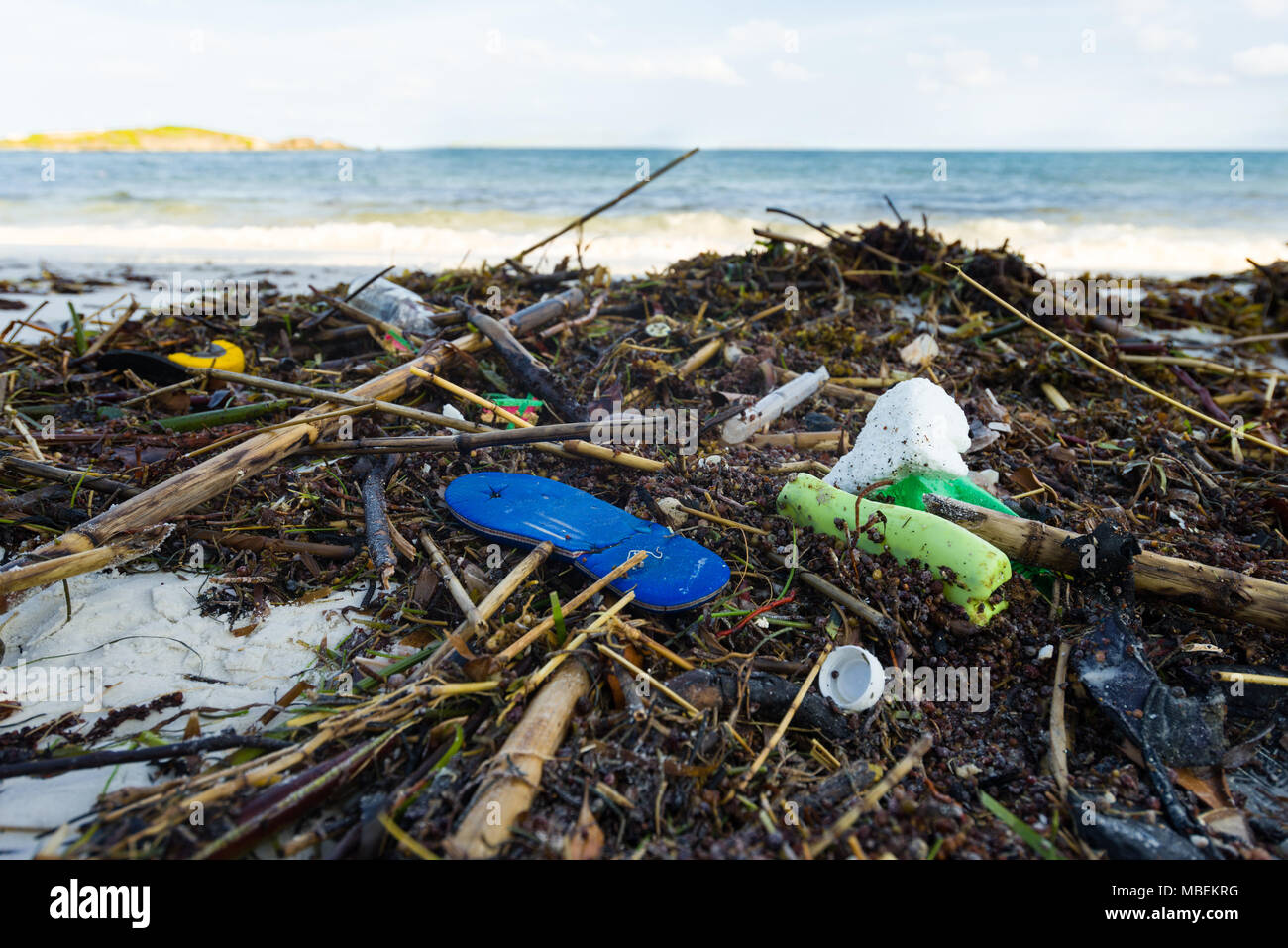 Plastic waste lies washed up on the shore of a white sand beach - Stock Image