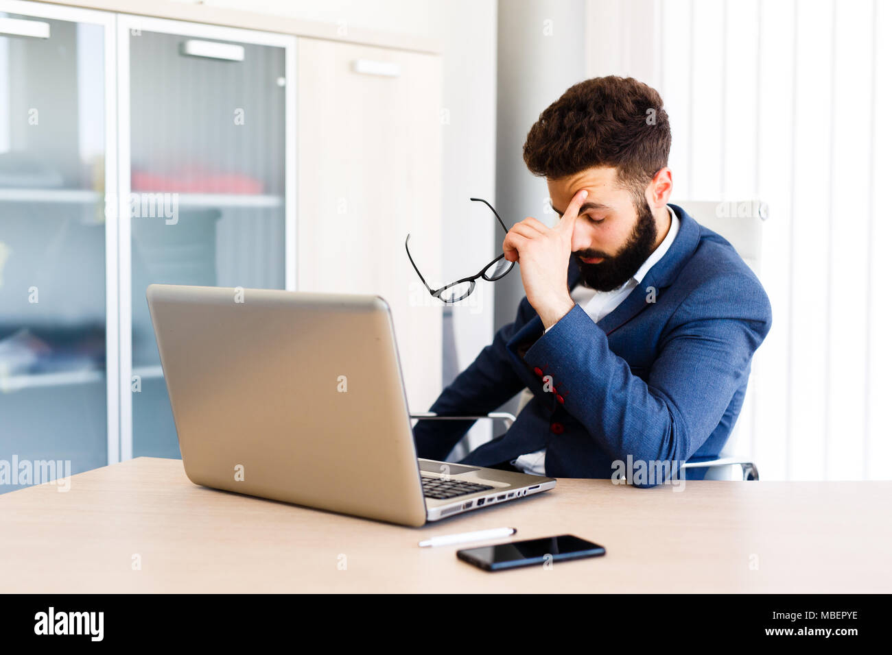 Young Businessman Has Stressful Day At Work - Stock Image