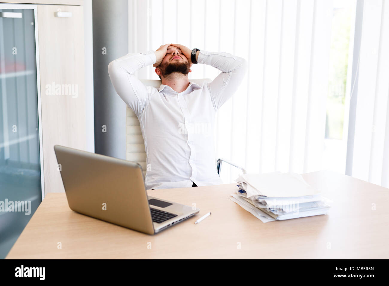 Young Businessman Has Very Stressful Day At Work - Stock Image