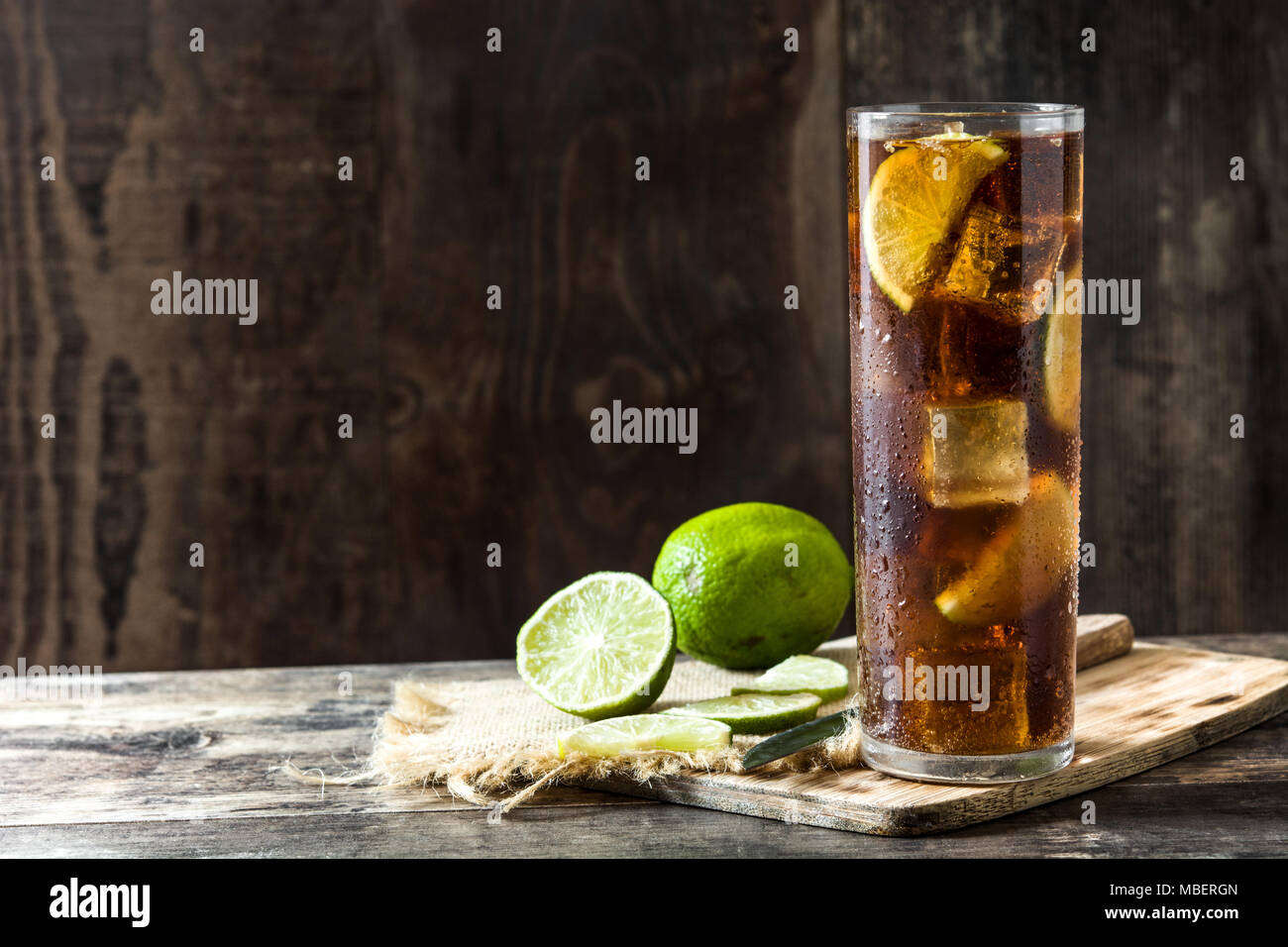 Cuba libre. Cocktail with rum, lime and ice on wooden table. - Stock Image