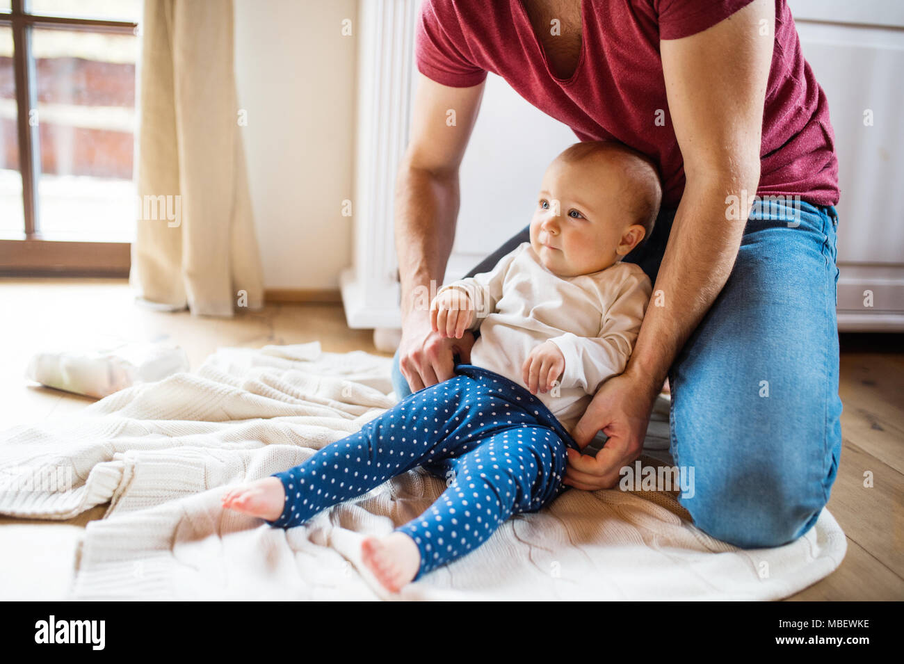 Unrecognizable father with a baby girl at home. Paternity leave. - Stock Image