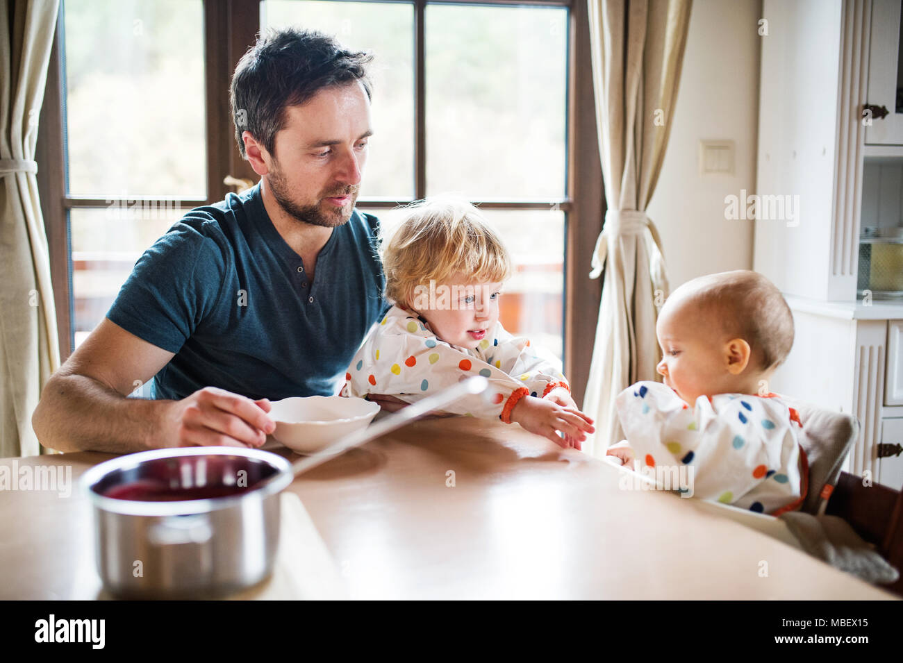 Father feeding two toddlers at home. Paternity leave. - Stock Image