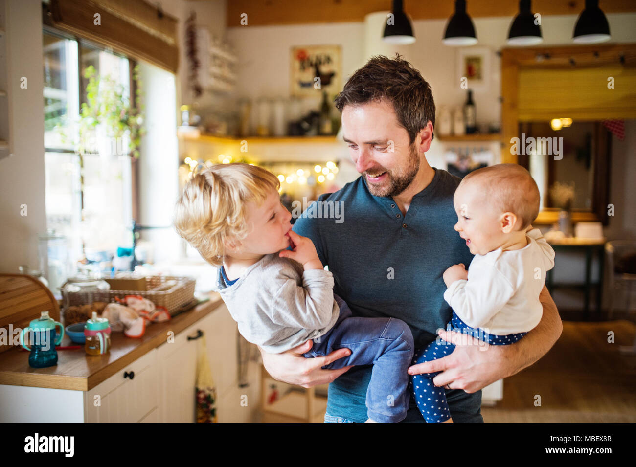Father holding two toddlers at home. Paternity leave. - Stock Image