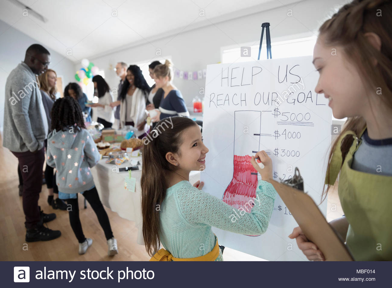 Girls filling in fundraising goal poster at bake sale in community center Stock Photo