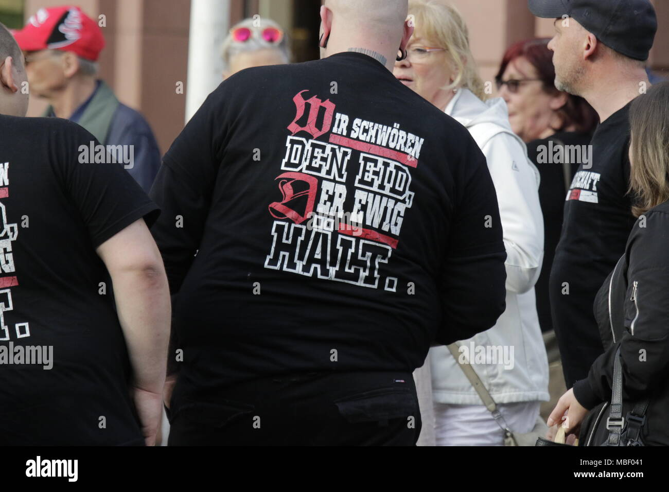 Mainz, Germany. 09th Apr, 2018. Members of the right-wing Kameradschaft Rheinhessen (comradeship Rhine-Hesse) can be seen at the protest, wearing t-shirts that read 'We swear the oath that lasts forever'. Around 50 right-wing protesters rallied in the city centre of Mainz, to protest against the German government, for the closing of the borders and against refugees under the slogan ÔMerkel has to goÕ. They were heckled by around 400 counter-protesters. Credit: Michael Debets/Pacific Press/Alamy Live News - Stock Image