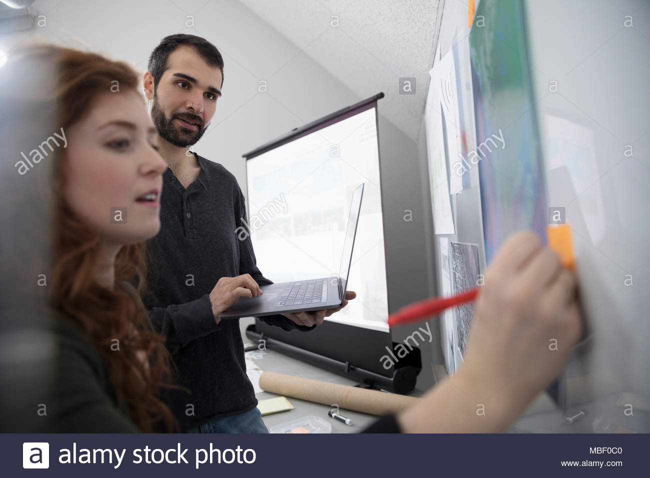 Creative designers editing poster on whiteboard - Stock Image