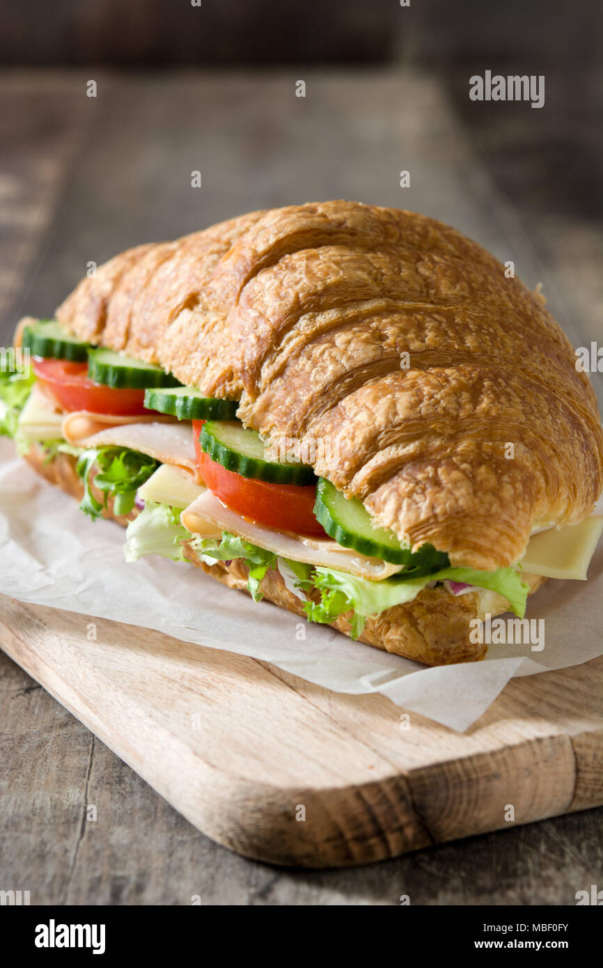 Croissant sandwich with cheese, ham and vegetables on wooden table - Stock Image