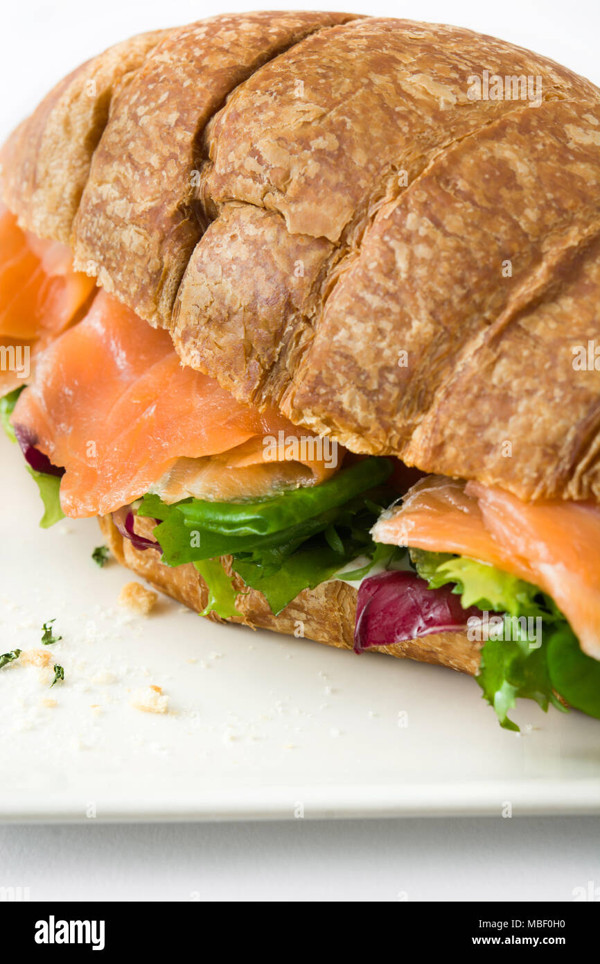 Croissant sandwich with salmon and vegetables isolated on white background Stock Photo