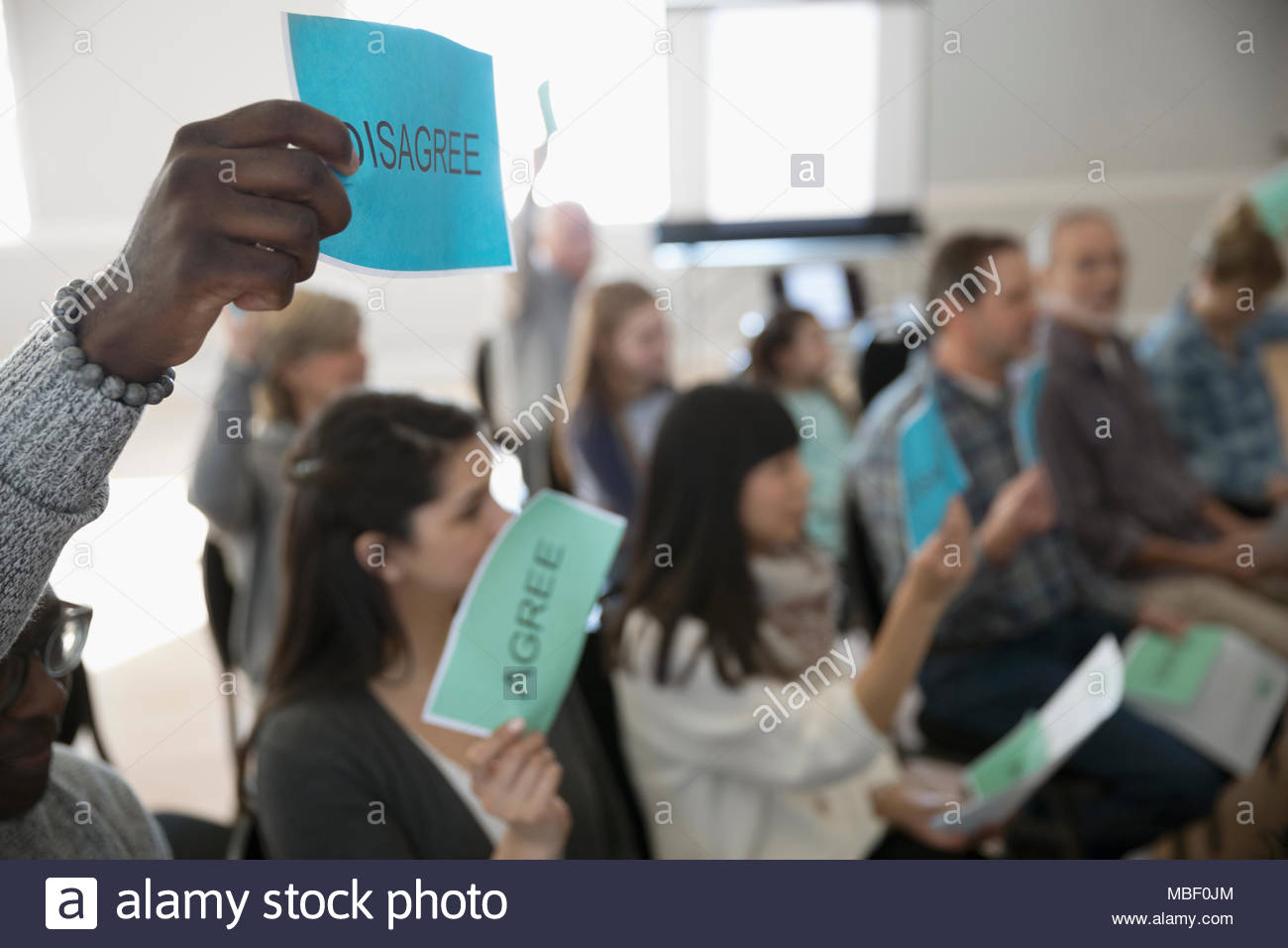 Audience voting with signs at town hall meeting - Stock Image