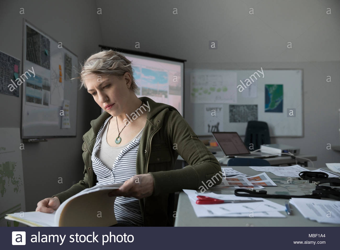 Focused female city planner working in office, reading paperwork - Stock Image