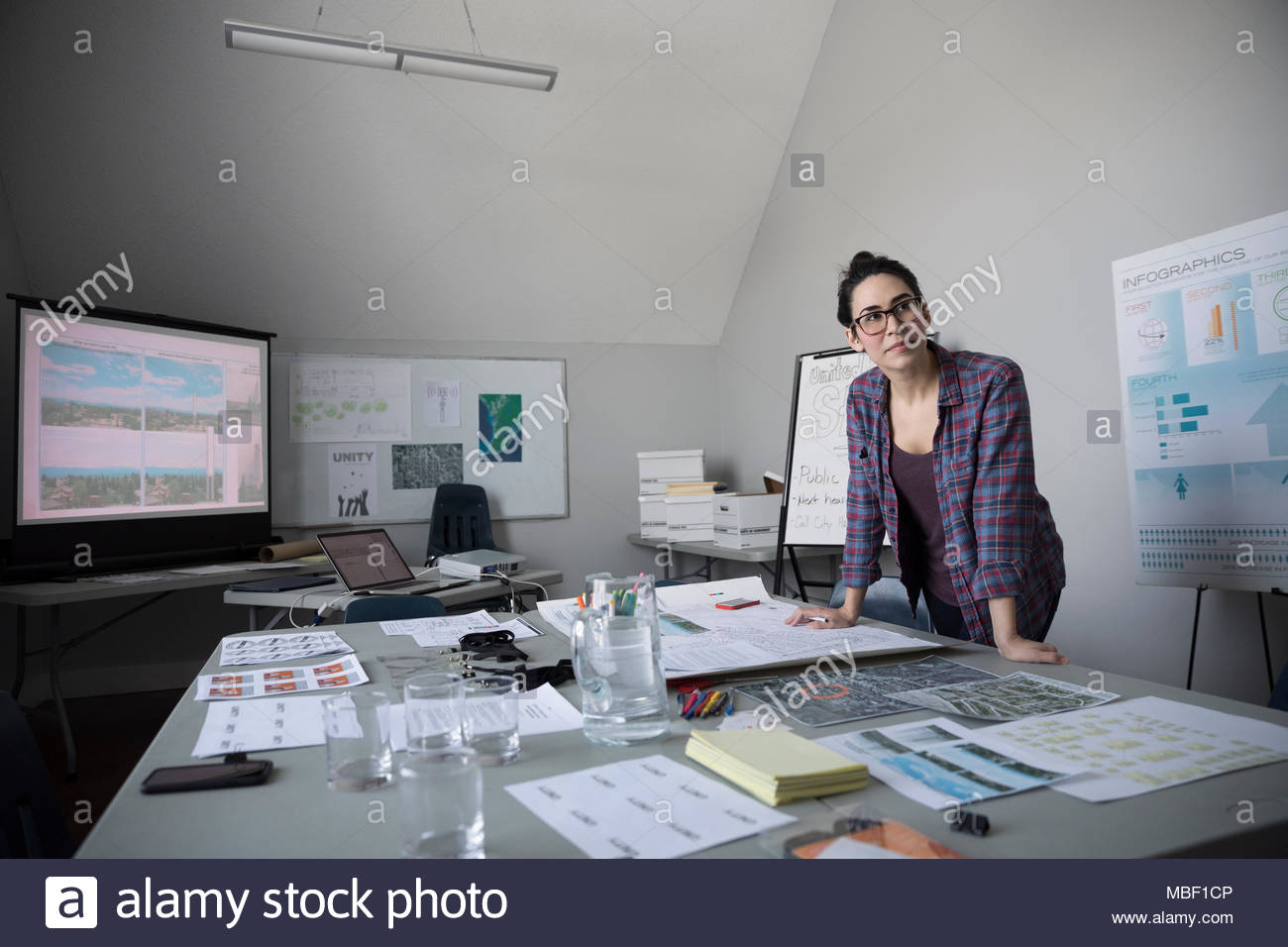 Female city planner reviewing blueprints, working in office - Stock Image
