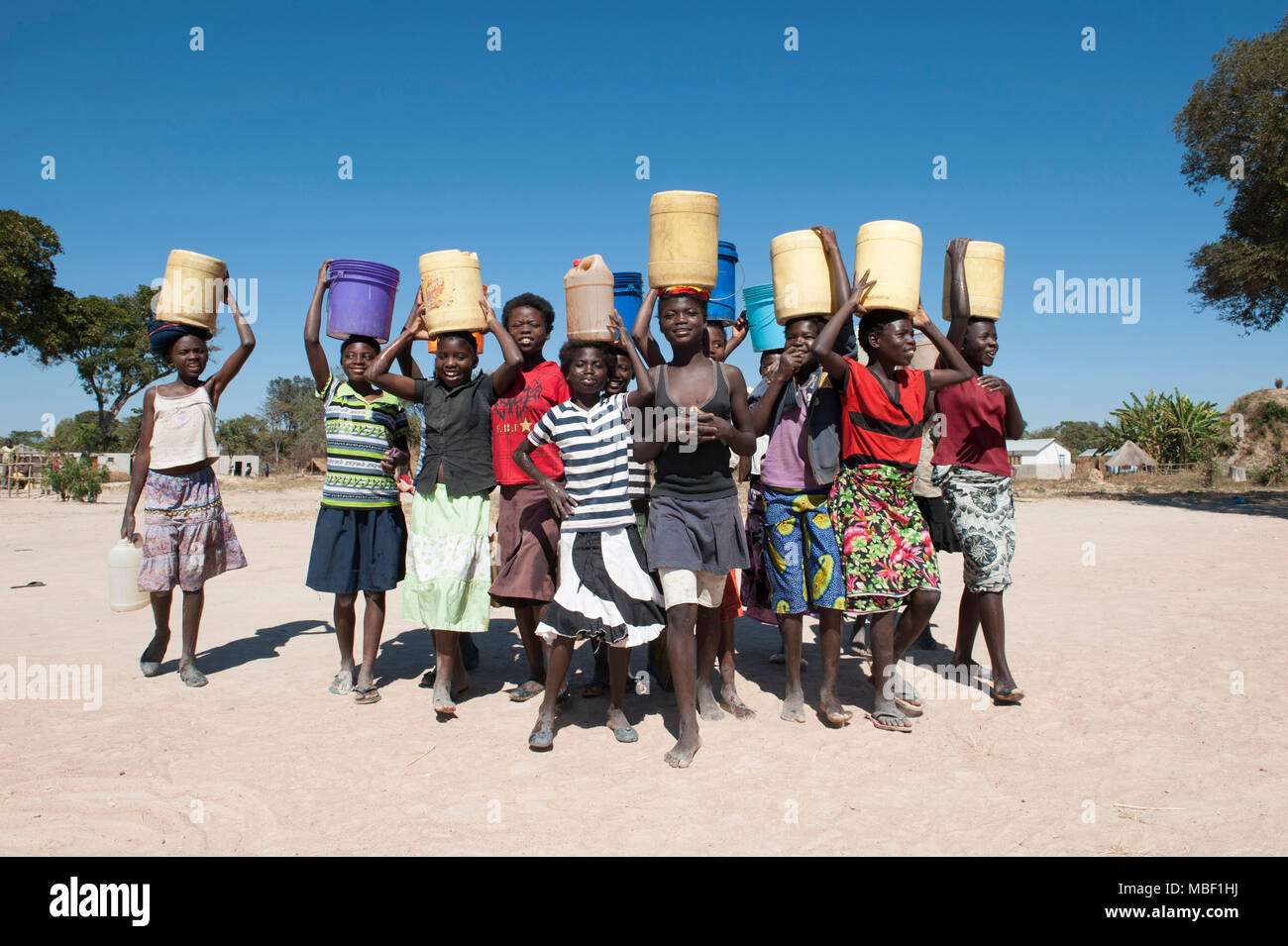 Zambian girls carrying water - Stock Image