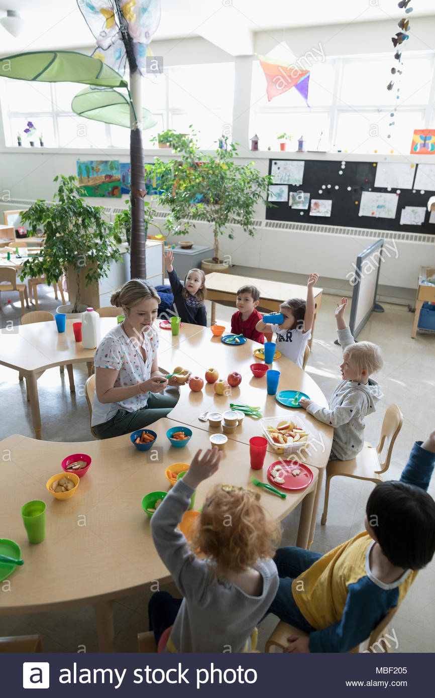 Preschool teacher and students eating during snack time in classroom - Stock Image