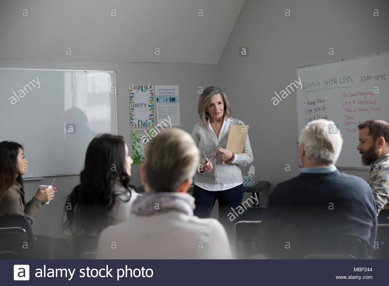 Woman with clipboard leading grief support group in community center - Stock Image