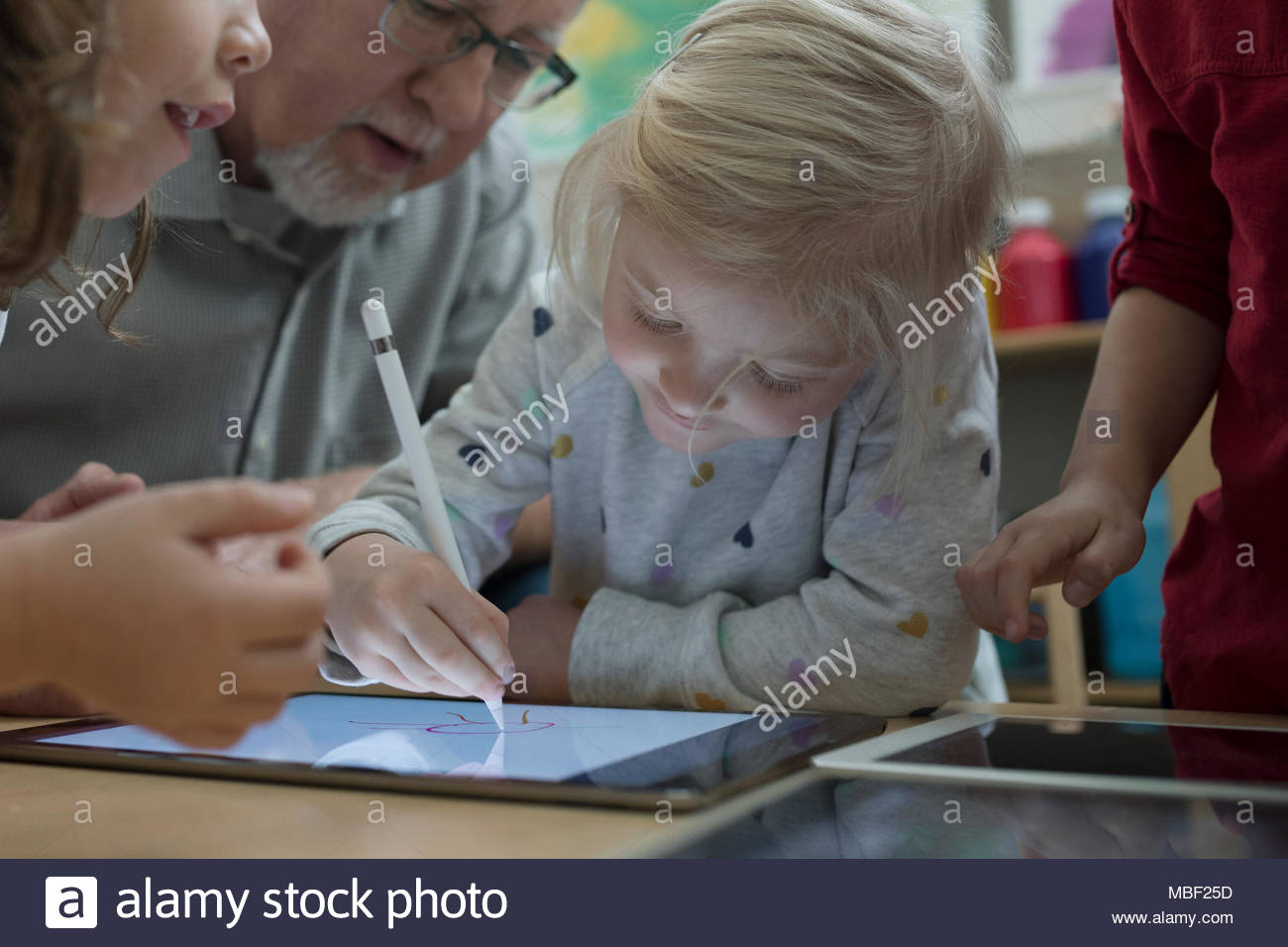 Close up preschool girl with stylus drawing on digital tablet - Stock Image