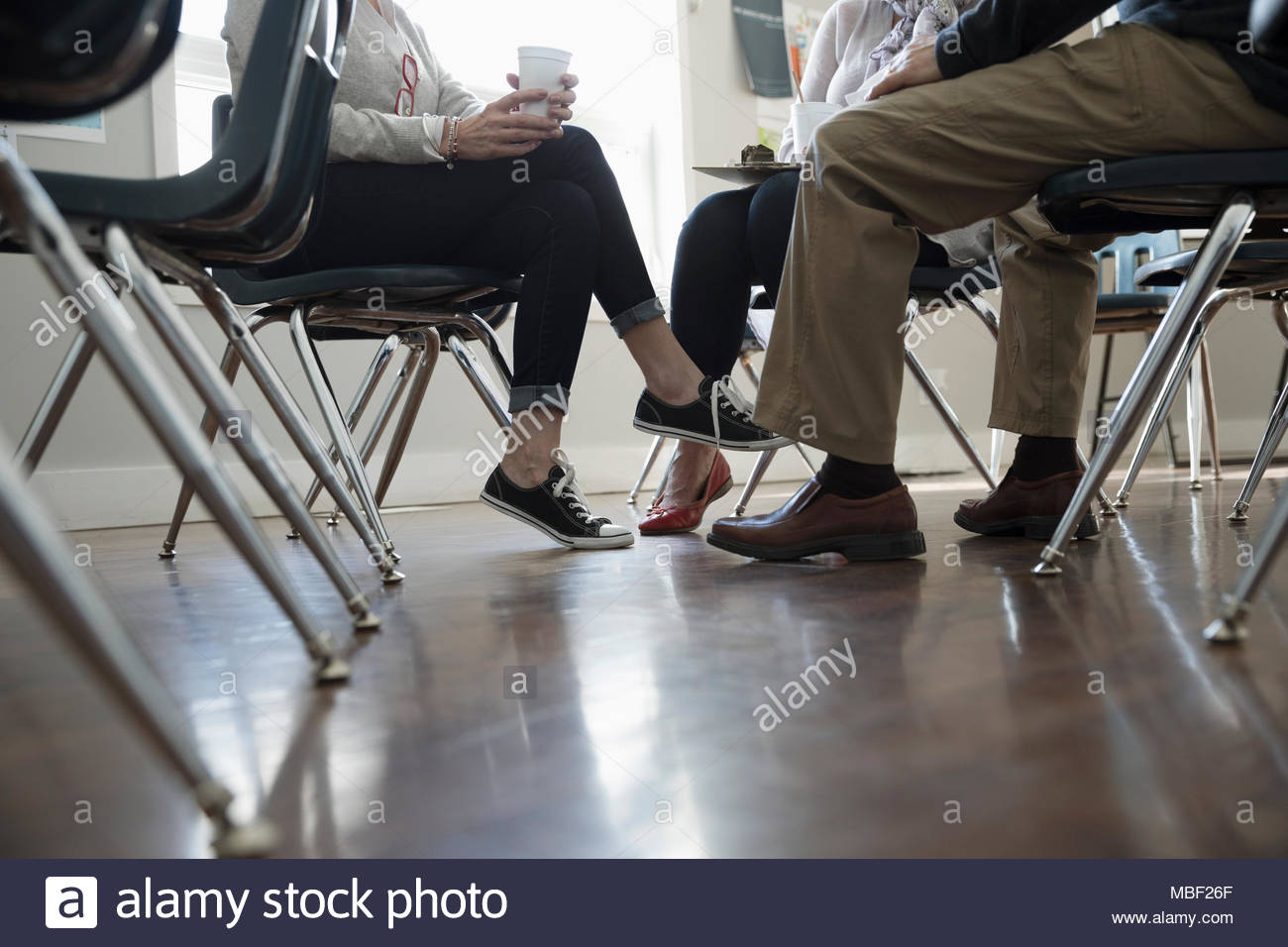 Support group talking, drinking coffee in community center - Stock Image