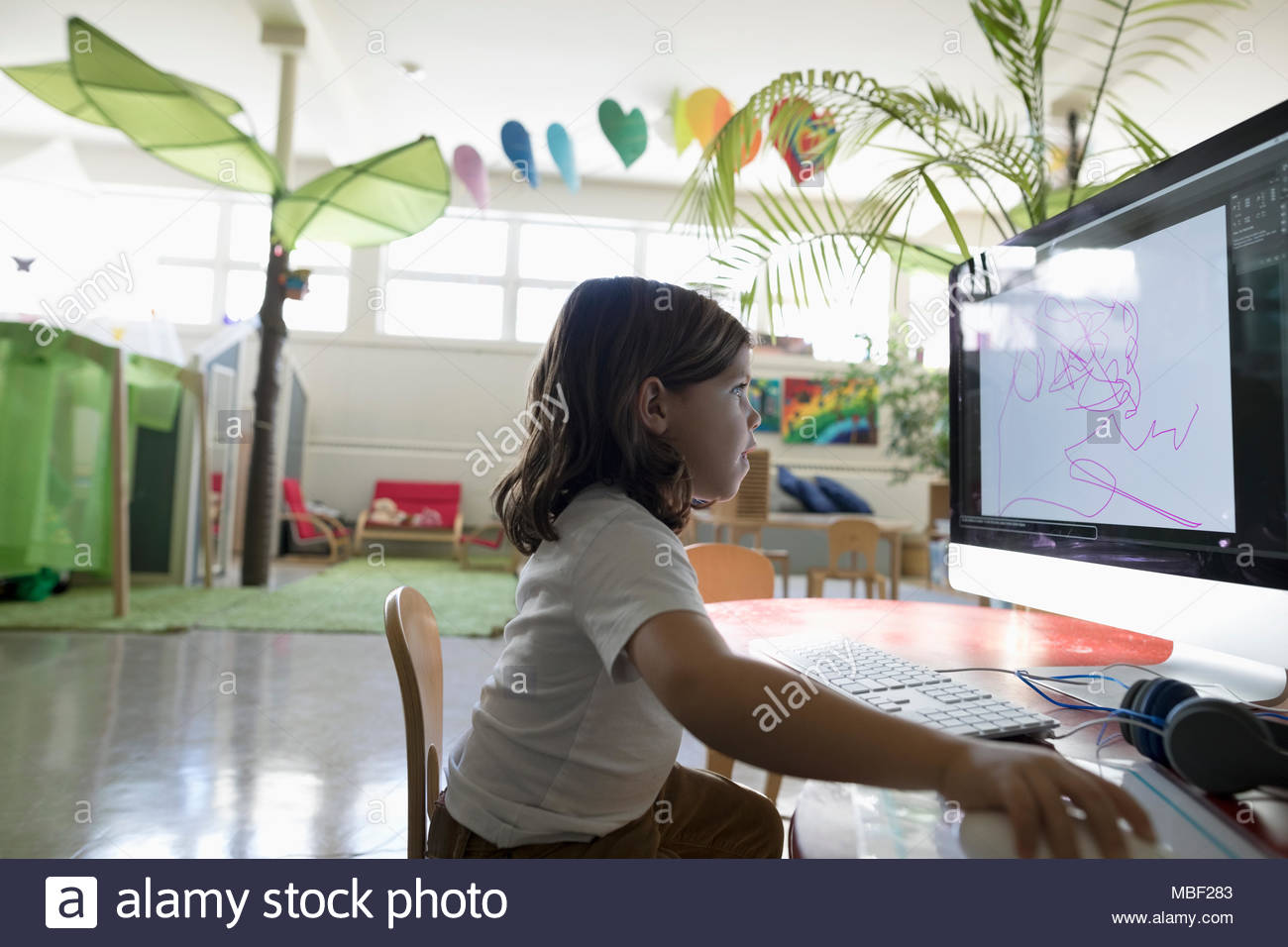 Preschool girl student drawing at computer in classroom - Stock Image
