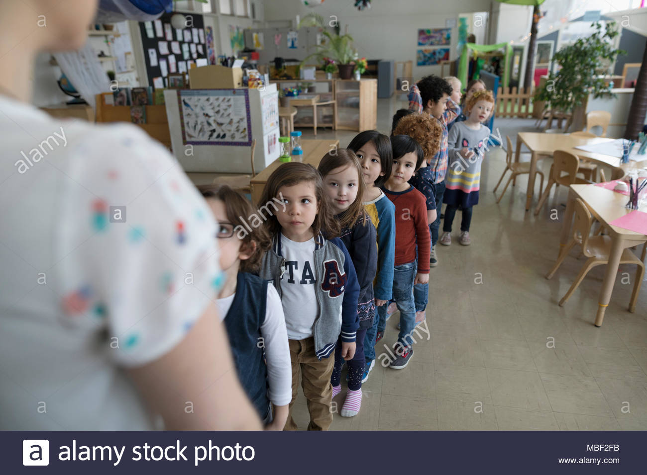 Preschool students lining up for teacher in classroom - Stock Image